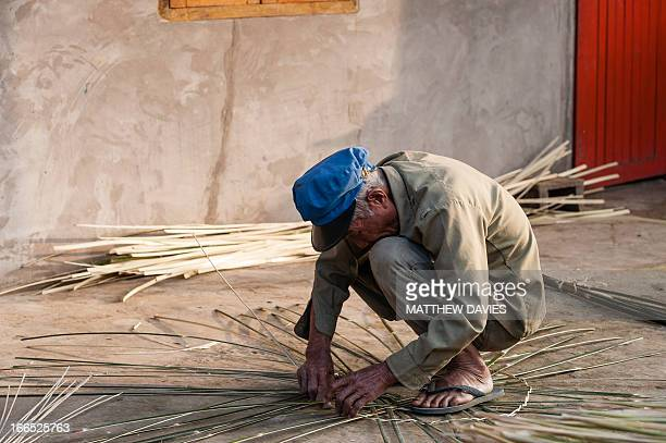 Old Lao Man Makes A Reed Basket While Squatting On The Floor In The Old Quater Of Phongsali In Norther Laos