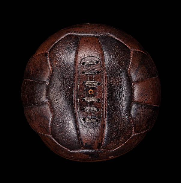 Old leather football on black
