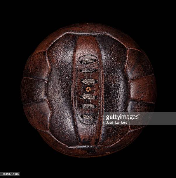 Old leather football on black