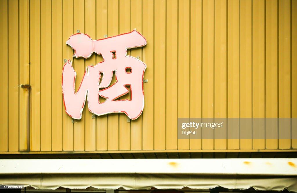 Old liquor sign on weathered wall above awning in Yokohama : Stock Photo