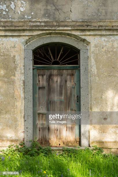 Old locked wooden door in a cracked wall