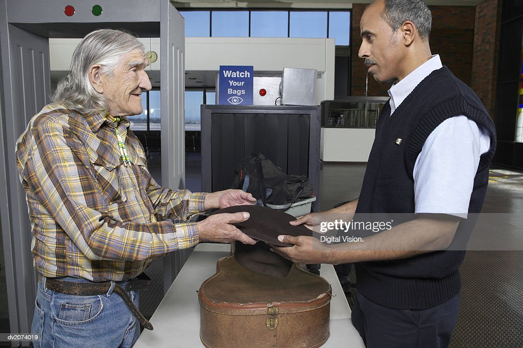 Old Male Cowboy at an Airport Security Check Showing a Customs Official His Empty Hat : Stock Photo