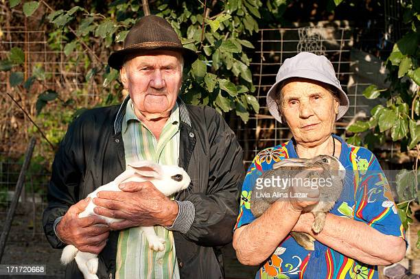 CONTENT] Old man and old woman holding rabbits