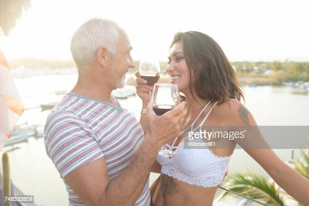 old man and young woman enjoying red wine on a balcony around sunset - may december romance stock photos and pictures