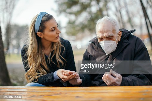 Old Man And Young Woman Sitting In Park And Talking High