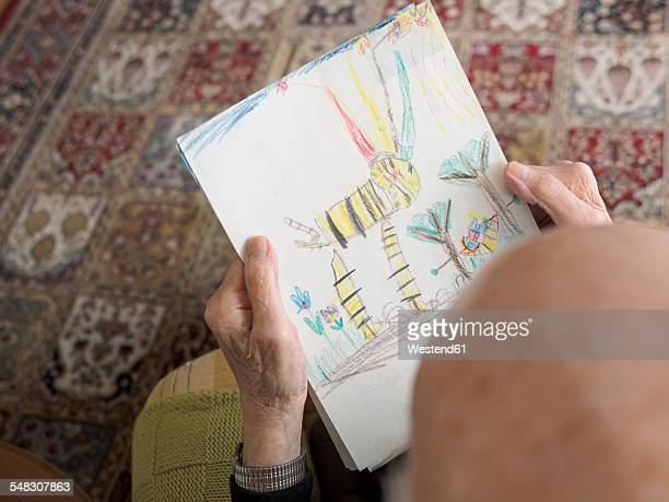 Old man at home looking at childs drawing