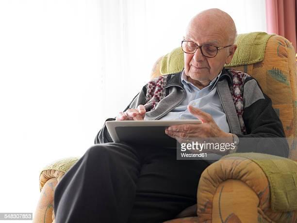 old man at home using digital tablet - einzelner senior stock-fotos und bilder