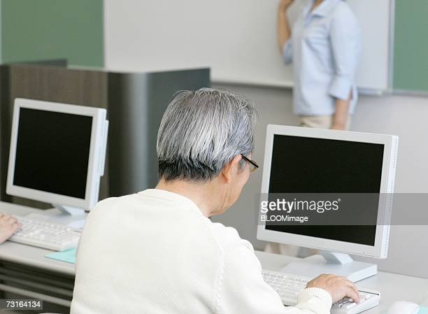 Old man attending computer class and studying