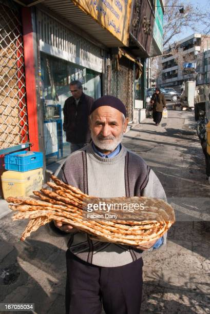 Old man bringing bread back home. Sangak is an iranian bread cooked on a bed of stones, thus its name .
