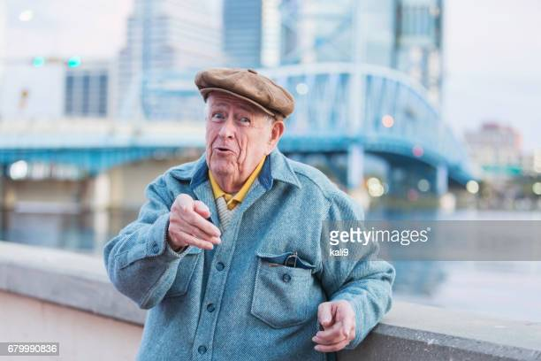 Old man by waterfront, pointing finger at camera
