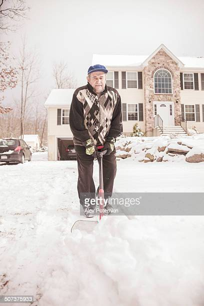 Old man cleaning doorway before house from snow after snowfall