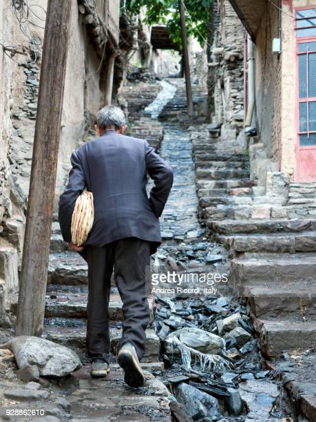 Old man climbing a steep alley in a village of northern Iran