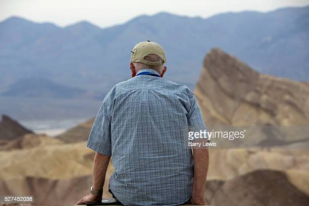 Old man contemplating Zabriski point part of Amargosa Range located in Death Valley National Park in California noted for its erosional landscape and...