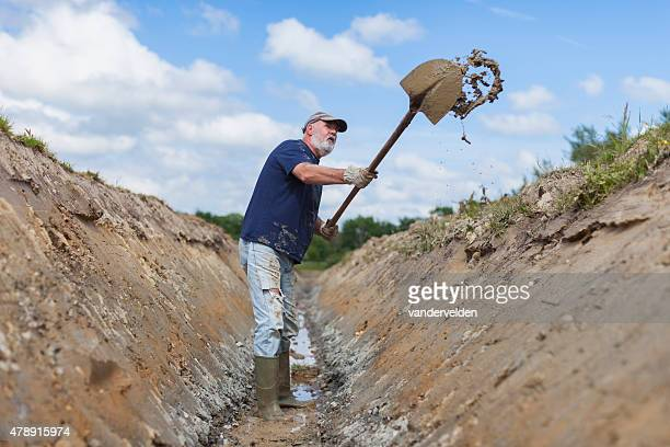 old man digging a ditch - ditch stock photos and pictures