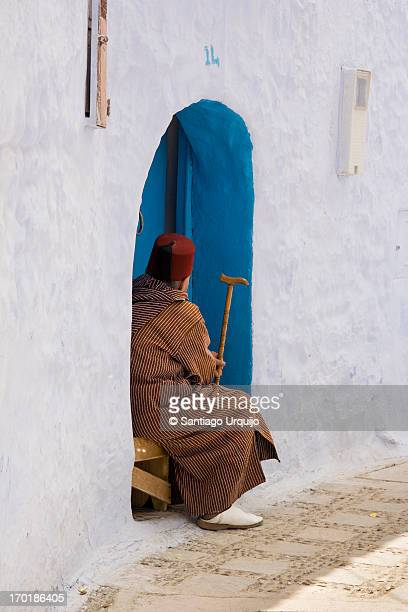 Old man dressed traditionally sitting in his house