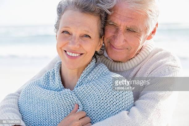 Old man embracing his happy wife from behind on the beach
