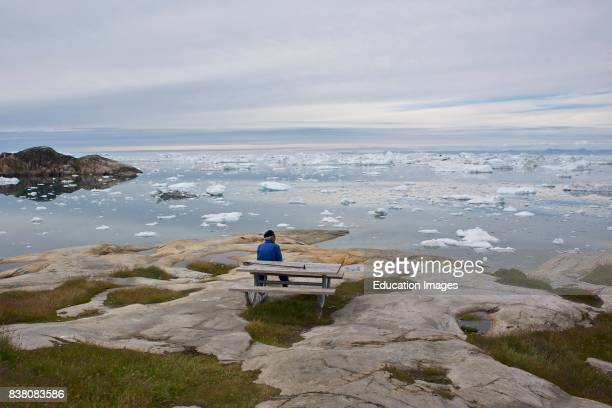 Old man enjoying the view over Ilulissat ice fjord and the Disko bay West Greenland The developments towards a modern society are moving fast in many...