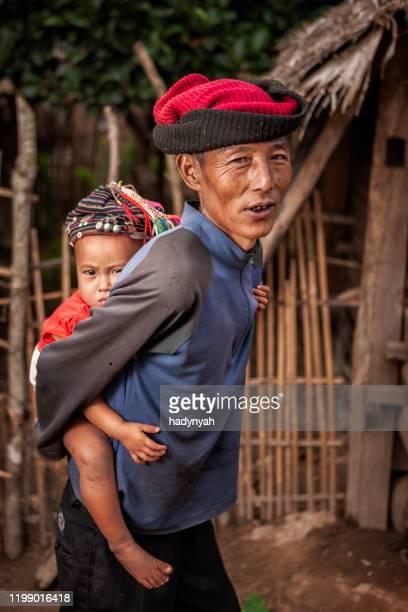 孫娘を運ぶ丘の部族の老人 - ラオス ストックフォトと画像