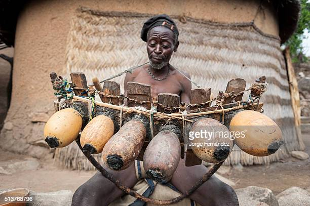 Old man from the Koma tribe playing the marimba an intrument made out of wood and calabashes