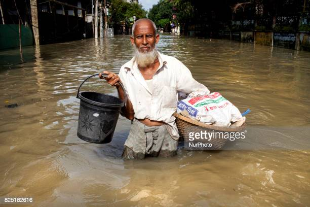 Old man going his home in water logging area July 26 2017 Chittagong Bangladesh Every day the Chittagong city is facing unmatched waterlogging this...