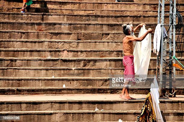 CONTENT] Old man hanging up curtains on the staircasas on the River Ganges