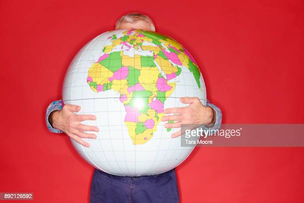 old man holding world globe - physical geography stock pictures, royalty-free photos & images
