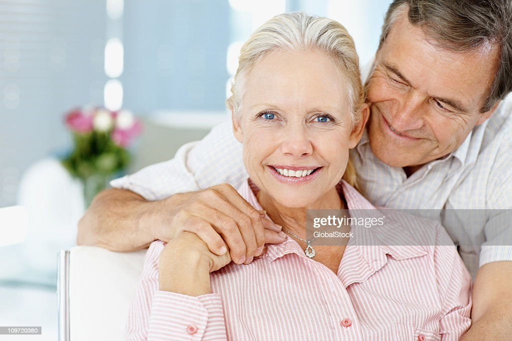 old man hugging a cute mature woman from behind stock photo | getty