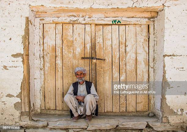 Old man in front of a closed door in the market badakhshan province ishkashim Afghanistan on August 9 2016 in Ishkashim Afghanistan
