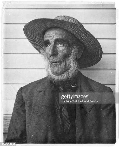 Old man in straw hat weathered face and beard standing in front of plain board wall 1922