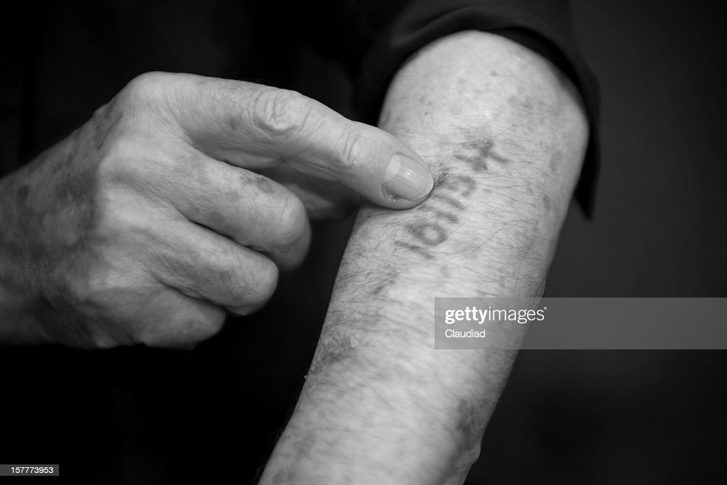 Old man is showing his number he got in Ausschwitz : Stock Photo