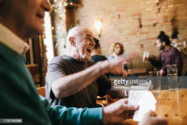 old man laughing during card game - playing card stock pictures, royalty-free photos & images