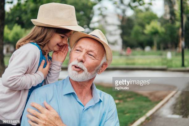 Old man listening his granddaughter whispering to him