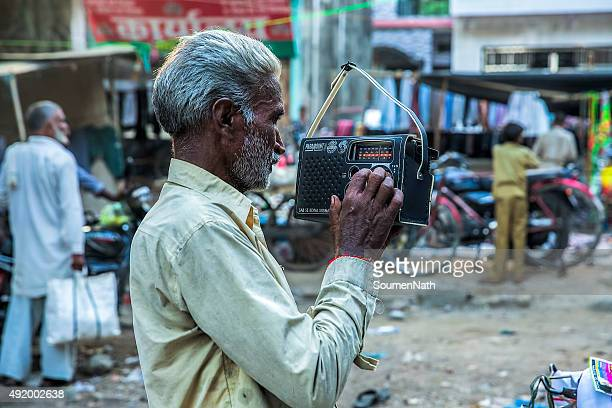 old man listening to an old fashioned radio set - radio stock pictures, royalty-free photos & images