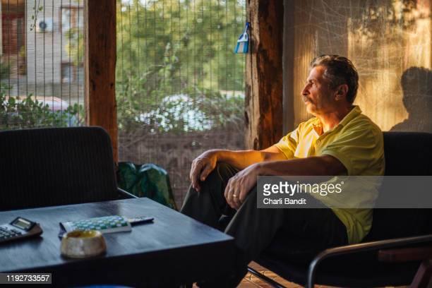 alter mann schaut aus dem fenster - einzelner senior stock-fotos und bilder