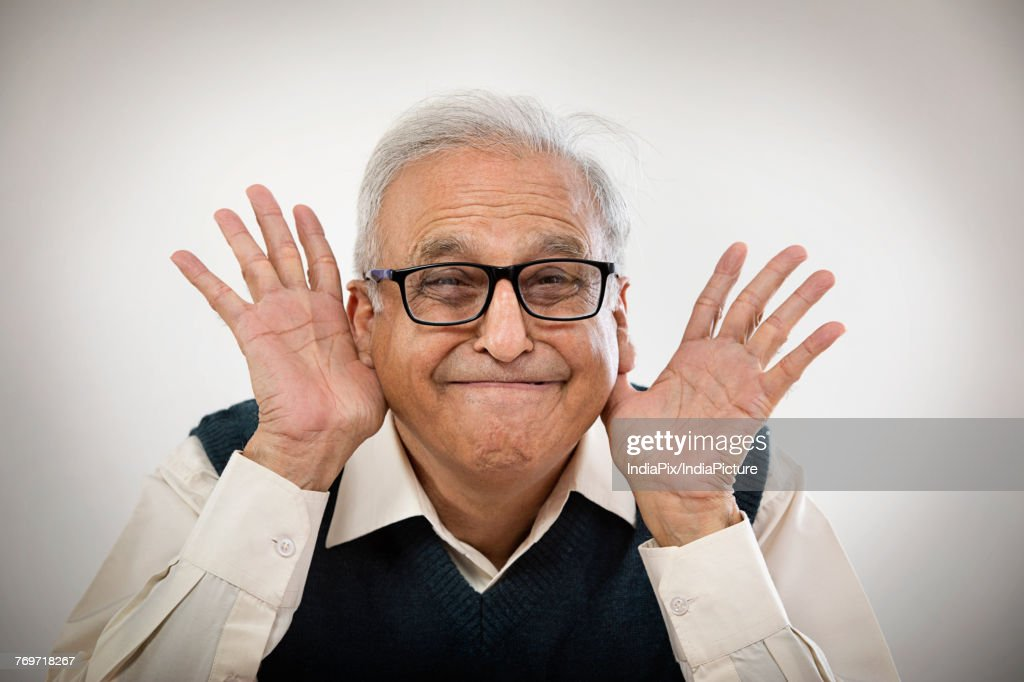 old man making funny face with hands in his ears ストックフォト
