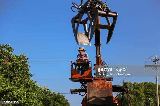 old man operating old forestry equipment to pick up hurricane irma debris; cape coral, fl, usa - 2017 hurricane irma stock pictures, royalty-free photos & images