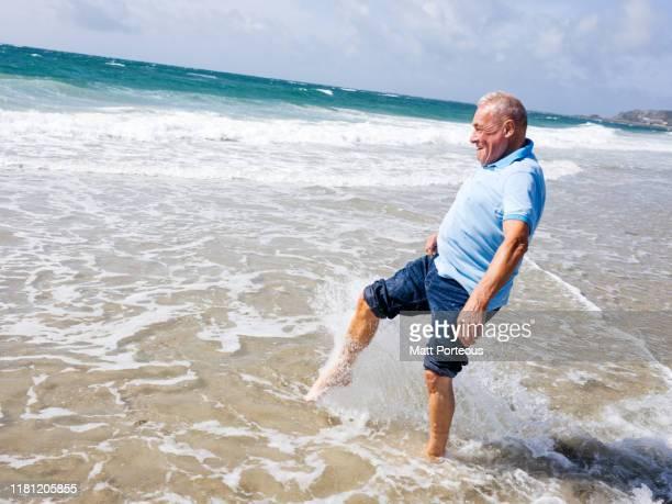 old man paddling in sea - un solo hombre fotografías e imágenes de stock