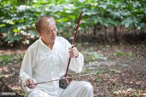 old man playing chinese traditional erhu