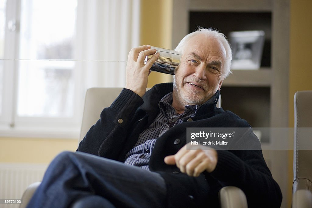old man playing with can phone : Stock Photo
