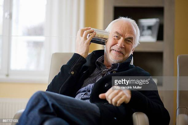 old man playing with can phone