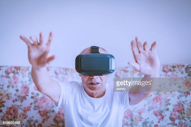Old man playing with VR