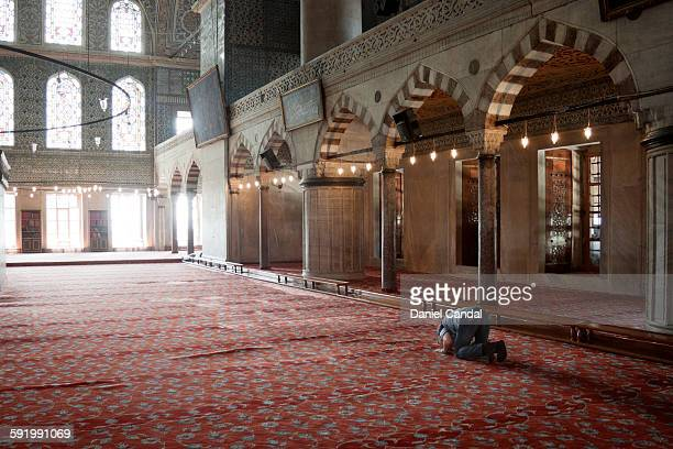 old man praying in the sultan ahmed mosque - moschee stock-fotos und bilder