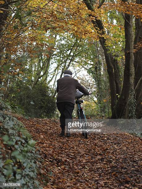 Old man pushing bicycle up a hill, Autumn, UK.