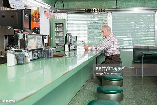 Old man reading in a diner