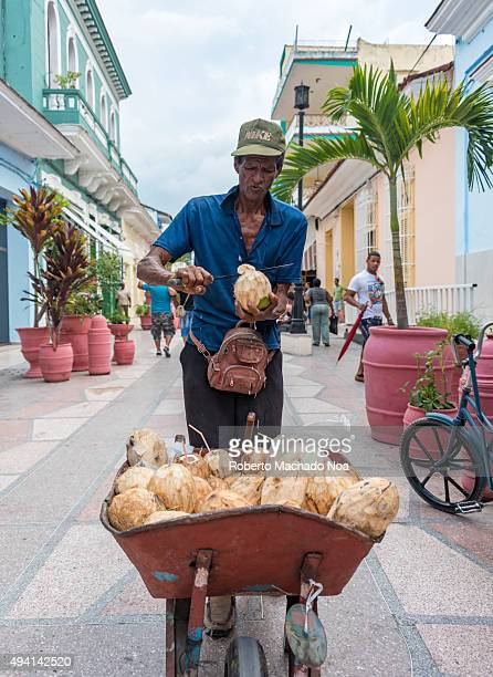 Old man selling coconut water in the streets of Sancti Spiritus Cuba Man slicing open a raw coconut with a sickle He is carrying the coconuts in a...