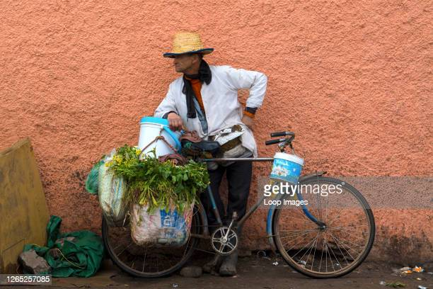 Old man selling vegetables and herbs from his old rusty blue bicycle in a Marrakesh food street market in Morocco.