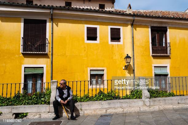Old man sit in front of colorful houses in the historic walled town
