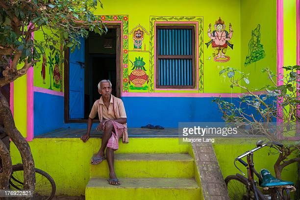 CONTENT] Old man sitting and resting in front of his colorful green painted house with traditional drawings of the Hindu god Jagannath in Raghurajpur...