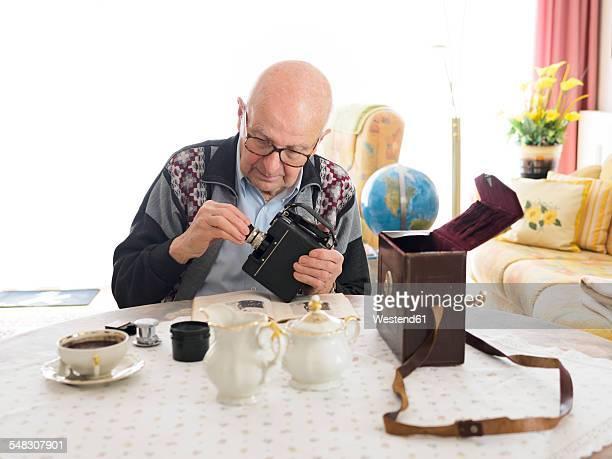 old man sitting at table dealing with old camera - einzelner senior stock-fotos und bilder