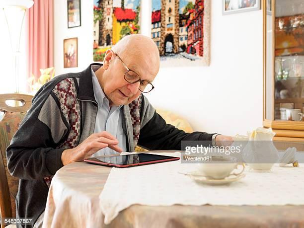old man sitting at table using digital tablet - einzelner senior stock-fotos und bilder